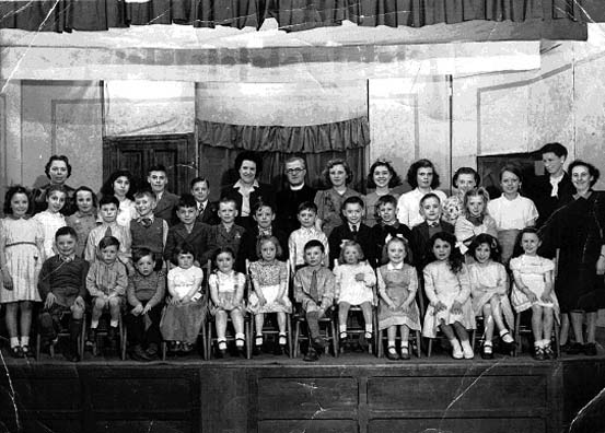 Children's Sunday School gathering onstage, circa 1947. The Rev E.J. Howells is pictured on the back row. Far left is Florrie Burrows and right are Elsie Moores and Nora Tootall.